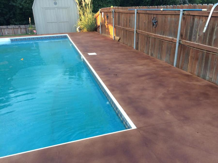 small stained concrete pool deck with wood fences in Fort Worth TX